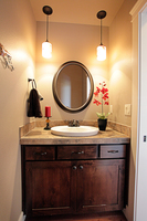 Thumb vanity  shaker style  knotty alder  dark color  rrecessed panel  two small drawers above two wide doors  standard overlay