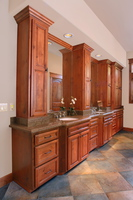 Thumb vanity  traditional style  knotty alder  medium color  raised panel doors  recessed panel drawers  towers   8 crown  clipped out sink sections with flutes  master bath  standard overlay