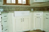 Thumb kitchen  traditional style  wide wainscot panel doors  apron front sink  wainscot columns or posts  painted with glaze