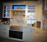 Thumb kitchen  contemporary style  painted with accent color walnut  recessed panel and savannah doors  glass doors  lighted glass back  open shelf  apron front sink  bank of drawers  taller toekick  hybrid construction   1