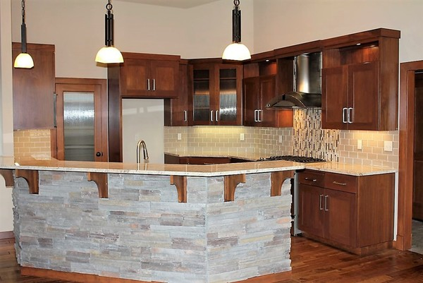 Bigthumb kitchen  contemporary style  walnut  dark color  recessed panel  full overlay  rock island back   4 bar supports  reeded glass doors  chimney style hood with top  open space at top of the uppers
