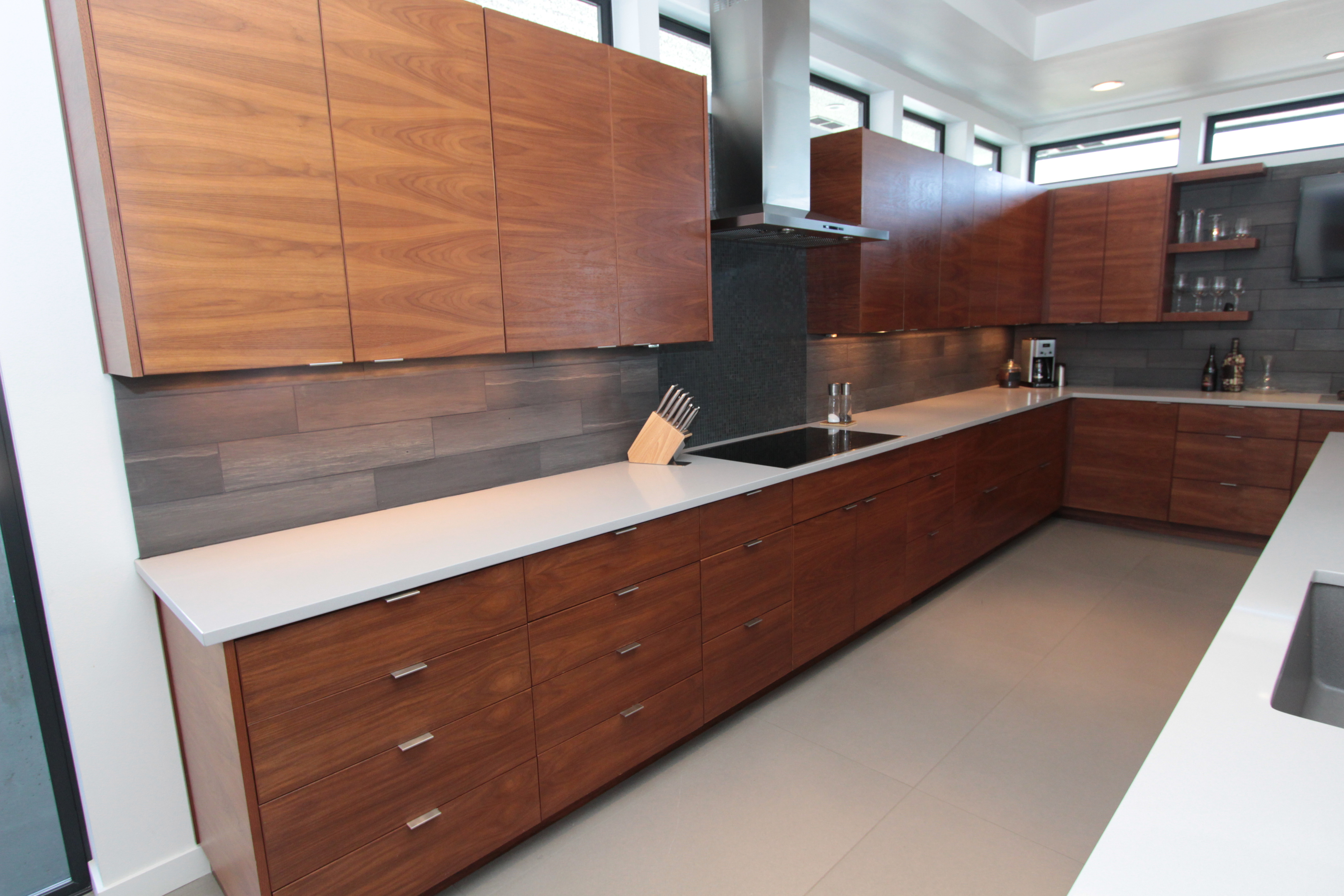 Kitchen  contemporary style  walnut  medium color  banded door  frameless construction  open shelves  shelves  chimney hood  bank of drawers  horizontal grain match