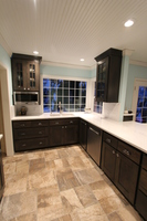 Thumb kitchen  craftsman style  knotty hickory  dark color  grey   recessed panel  wide rail  glass doors with grids  joint grooves on doors  wood hood  peninsula  to celing  standard overlay
