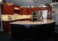 Thumb kitchen  traditional style  cherry  raised panel  cherry color  half arch glass doors  double oven  accent color black painted island  angled island  staggered uppers  plate rods  metal nailheads on island doors