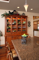 Thumb kitchen  traditional style  knotty alder  medium color  raised panel  china area  glass doors  turned posts  flutes  full overlay