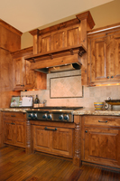 Thumb kitchen  traditional style  knotty alder  medium color  raised panel  flush mount  wood hood  posts at rangetop