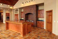Thumb kitchen  traditional style  knotty cherry  medium color  t shaped raised panel doors  raised bar with posts    legs   columns  stone arch cooking space  standard overlay  wood island top