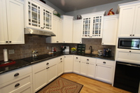 Thumb kitchen  traditional style  painted  recessed panel  glass grid doors  9 light or praire grid  staggered height  diagonal corner base   upper  full overlay